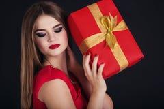 La muchacha bonita está sosteniendo la caja de regalo, tiempo de la Navidad Imágenes de archivo libres de regalías
