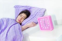La muchacha bonita está despertando y mirada en el reloj Fotografía de archivo