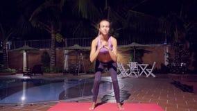 La muchacha bonita hace ejercicios de la aptitud cerca de piscina por la tarde almacen de metraje de vídeo