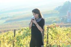 La muchacha bonita huele el aroma del buen vino Imagenes de archivo