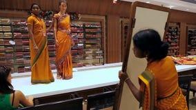 La muchacha bonita intenta encendido la sari del vestido de Oriente contra el espejo metrajes