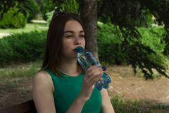 La muchacha bonita joven bebe el agua dulce, al aire libre Fotos de archivo libres de regalías