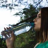 La muchacha bonita joven bebe el agua dulce, al aire libre Imagen de archivo