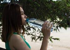 La muchacha bonita joven bebe el agua dulce, al aire libre Imagen de archivo libre de regalías