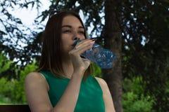 La muchacha bonita joven bebe el agua dulce, al aire libre Imagenes de archivo