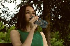 La muchacha bonita joven bebe el agua dulce, al aire libre Imágenes de archivo libres de regalías