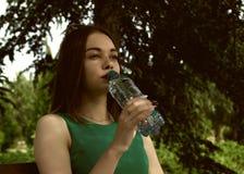 La muchacha bonita joven bebe el agua dulce, al aire libre Fotografía de archivo libre de regalías
