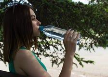 La muchacha bonita joven bebe el agua dulce, al aire libre Foto de archivo libre de regalías