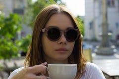 La muchacha bonita joven bebe una taza de bebida caliente, al aire libre Foto de archivo