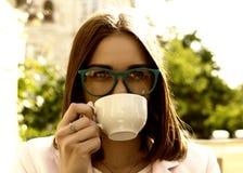 La muchacha bonita joven bebe una taza de bebida caliente, al aire libre Fotos de archivo libres de regalías