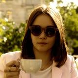 La muchacha bonita joven bebe una taza de bebida caliente, al aire libre Imágenes de archivo libres de regalías