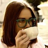 La muchacha bonita joven bebe una taza de bebida caliente, al aire libre Imagen de archivo libre de regalías