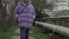 La muchacha bonita joven camina, tiempo al aire libre, frío almacen de video