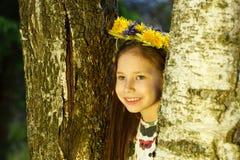La muchacha bonita joven en guirnalda de las flores está mirando fuera de árbol de abedul Imagen de archivo