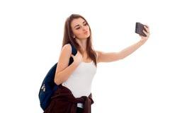 La muchacha bonita joven en la camisa blanca y con una mochila hace la foto en el teléfono aislado en el fondo blanco Foto de archivo libre de regalías