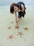 La muchacha bonita joven escoge estrellas de mar Imagenes de archivo