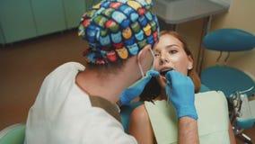 La muchacha bonita joven está en gabinete dental en el tratamiento y consultating 4K almacen de metraje de vídeo