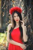 La muchacha bonita joven está presentando con las flores Imagen de archivo libre de regalías