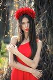 La muchacha bonita joven está presentando con las flores Fotos de archivo