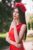 La muchacha bonita joven está presentando con las flores Foto de archivo