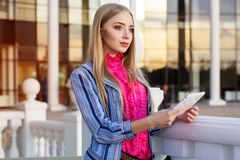 La muchacha bonita joven está sosteniendo su tableta Fotos de archivo libres de regalías