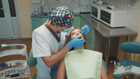 La muchacha bonita joven est? en gabinete dental en el tratamiento y consultating almacen de metraje de vídeo