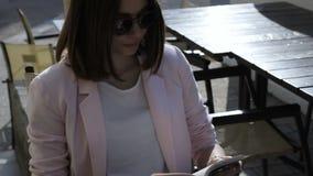 La muchacha bonita joven lee un libro, al aire libre almacen de video