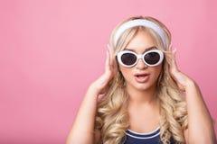 La muchacha bonita joven linda que sorprende en el fondo rosado come las palomitas y la mirada de la cámara, llevando un swimsuit imágenes de archivo libres de regalías