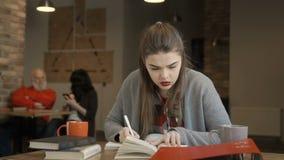 La muchacha bonita joven se prepara a los exámenes almacen de video