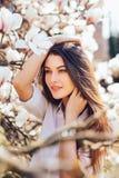 La muchacha bonita joven se relaja en el jardín hermoso de las magnolias rosadas que florecen el estación de primavera Imágenes de archivo libres de regalías