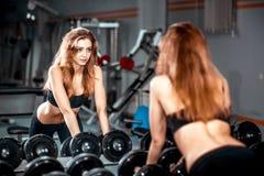 La muchacha bonita joven se resuelve en el gimnasio Fotos de archivo