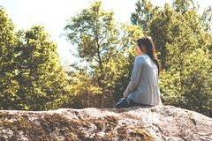 La muchacha bonita joven se sienta en una roca grande y admira la naturaleza imágenes de archivo libres de regalías