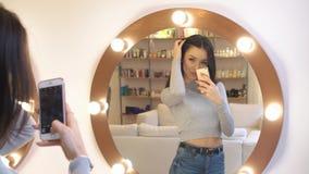 La muchacha bonita joven toma una foto de sí misma antes del espejo ella en el salón de belleza con la reflexión fantástica en el almacen de metraje de vídeo