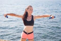 La muchacha bonita juega deportes con pesas de gimnasia en la playa en el mar Imagen de archivo libre de regalías