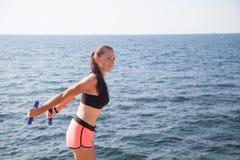 La muchacha bonita juega deportes con pesas de gimnasia en la playa en el mar Fotografía de archivo libre de regalías