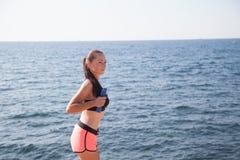 La muchacha bonita juega deportes con pesas de gimnasia en la playa en el mar Fotos de archivo