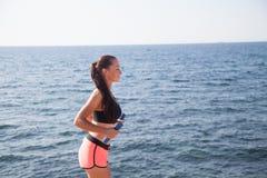 La muchacha bonita juega deportes con pesas de gimnasia en la playa en el mar Imagen de archivo