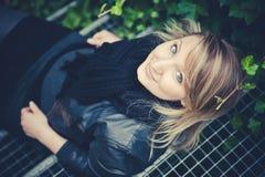 La muchacha bonita la mentira rubia en los pasos de las escaleras del metal y mira para arriba Fotos de archivo