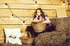 La muchacha bonita lee el libro fotos de archivo