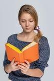 La muchacha bonita lee el libro Foto de archivo libre de regalías