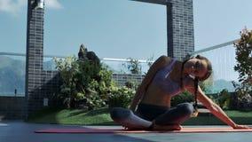 La muchacha bonita lleva a cabo la actitud de la yoga que se sienta en karemat rojo
