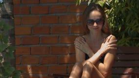 La muchacha bonita mancha la protección solar que se sienta en silla de cubierta