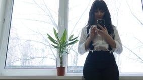 La muchacha bonita miente en un sofá con SMS de charla del teléfono celular que hojea Internet almacen de video