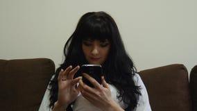 La muchacha bonita miente en un sofá con SMS de charla del teléfono celular que hojea Internet metrajes