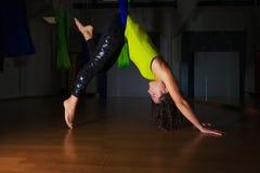 La muchacha bonita practica la posición antigravedad de la yoga en gimnasio respecto a un azul Foto de archivo