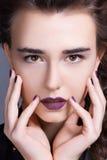La muchacha bonita presiona sus manos a su cara Imágenes de archivo libres de regalías