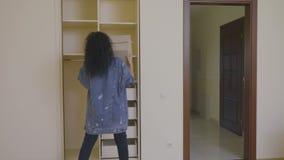 La muchacha bonita puso una caja con cosas en un guardarropa vacío en una nueva casa almacen de metraje de vídeo