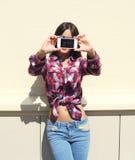 La muchacha bonita que lleva una camisa a cuadros hace el autorretrato de la foto en el smartphone al aire libre Imagenes de archivo
