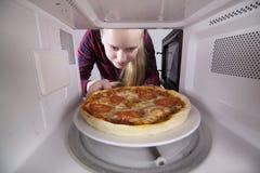 La muchacha bonita que mira en microonda está sosteniendo la placa con la pizza Imagen de archivo
