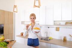 La muchacha bonita que presenta y come las patatas fritas, se coloca en el centro de ki Imagen de archivo